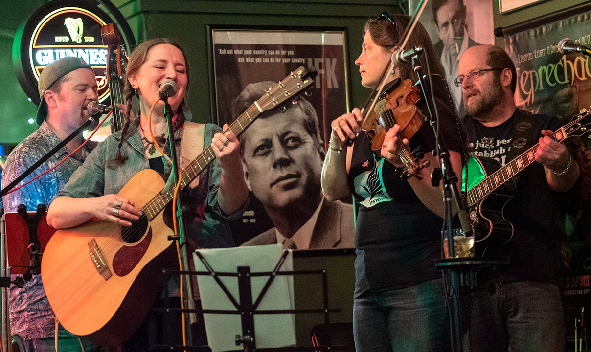 A picture of the band, two men on the edges and two women in the middle, holding various instruments, with a photo of JFK against the wall right in the middle.